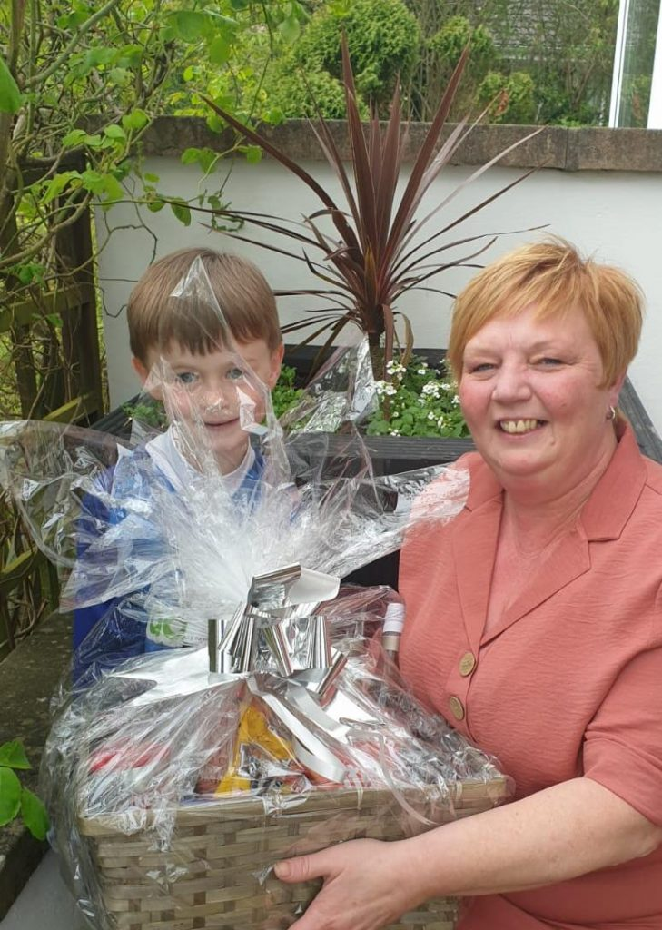 Ryan presenting the hamper to Mrs Rodgers